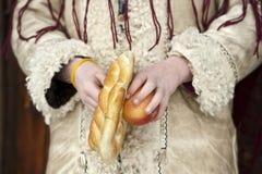 Feche acima das mãos que guardaram a maçã e o pretzel de uma criança vestida no desgaste romeno tradicional Imagem de Stock Royalty Free