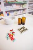 Feche acima das medicinas e do frasco perto de um almofariz Imagens de Stock