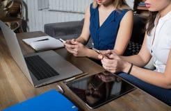Feche acima das meninas de uns dois modernos que têm o bate-papo em linha em telefones celulares após o trabalho no laptop imagem de stock royalty free