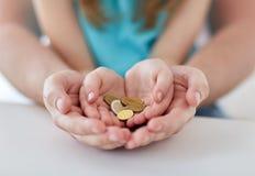 Feche acima das mãos da família que guardam euro- moedas do dinheiro Imagens de Stock
