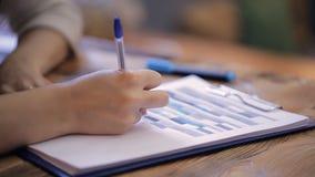 Feche acima das mãos da mulher que escrevem o enchimento na tabela no dobrador dentro do escritório video estoque