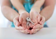 Feche acima das mãos do homem e da menina com chaves da casa Foto de Stock