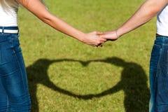 Feche acima das mãos dos pares junto com o sinal do amor. Imagens de Stock Royalty Free