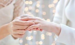Feche acima das mãos lésbicas dos pares com aliança de casamento Imagem de Stock