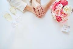 Feche acima das mãos lésbicas e das alianças de casamento dos pares Imagem de Stock