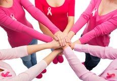 Feche acima das mulheres com as fitas da conscientização do câncer foto de stock