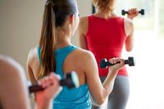 Feche acima das mulheres com pesos no gym imagem de stock royalty free