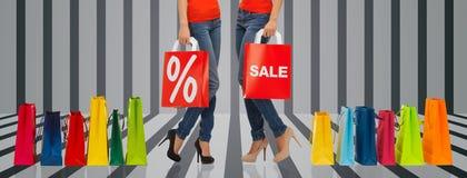 Feche acima das mulheres com sinal da venda no saco de compras imagem de stock