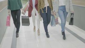 Feche acima das mulheres que vestem estilos diferentes da roupa e das sapatas que andam na alameda que guarda sacos de compras - filme