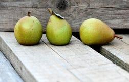 Feche acima das peras verdes na prancha de madeira com fundo de madeira imagens de stock royalty free