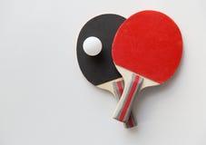 Feche acima das raquetes de tênis de mesa com bola Fotografia de Stock Royalty Free