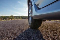 Feche acima das rodas de carro na estrada asfaltada foto de stock royalty free