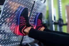 Feche acima das sapatas de uma jovem mulher do ajuste que faz a imprensa do pé no gym fotografia de stock