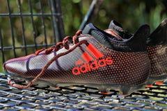 Feche acima das sapatas do futebol, tipo famoso de roupas desportivos 'Adidas ' fotografia de stock