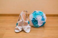 Feche acima das sapatas do ramalhete e da noiva do casamento Fotografia de Stock