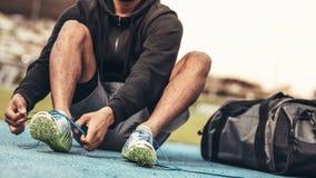 Feche acima das sapatas vestindo de um atleta fotos de stock royalty free