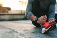 Feche acima das sapatas vestindo de um atleta fotos de stock