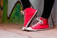 Feche acima das sapatilhas vermelhas vestidas por um adolescente. imagem de stock