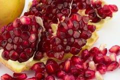 Feche acima das sementes da romã no branco Fotografia de Stock Royalty Free