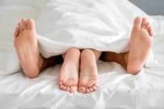 Feche acima das solas dos pés dos pares na cama branca Fotografia de Stock