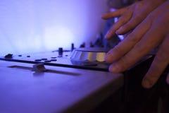 Feche acima das trilhas de mistura de um DJ da música em seu console eletrônico Fotografia de Stock Royalty Free