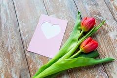Feche acima das tulipas e do cartão com coração Fotos de Stock Royalty Free
