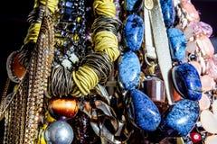 Feche acima das várias colares brilhantes da mulher com fundo preto Foco seletivo Fotografia de Stock Royalty Free