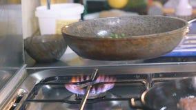 Feche acima de agitar espinafres na frigideira com óleo lentamente filme