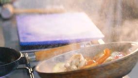 Feche acima de agitar vegetais na frigideira com óleo lentamente vídeos de arquivo