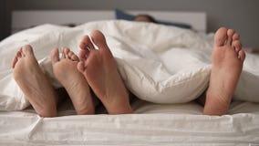 Feche acima de bonito novo e o jogo de amor dos pares e para dançar seus pés sob o quando geral acorda na cama na manhã video estoque