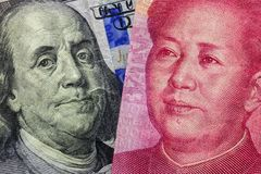 Feche acima de cem dólares e de 100 cédulas de Yaun com foco em retratos de Benjamin Franklin e de Mao Zedong /USA contra China t Imagem de Stock