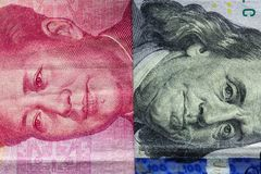 Feche acima de cem dólares e de 100 cédulas de Yaun com foco em retratos de Benjamin Franklin e de Mao Zedong /USA contra China t Fotografia de Stock Royalty Free