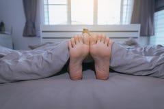Feche acima de com os pés descalços, os pés e o estiramento preguiçosamente na cama após acordar Fotos de Stock