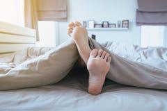 Feche acima de com os pés descalços, os pés e o estiramento preguiçosamente na cama após acordar Fotos de Stock Royalty Free