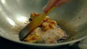 Feche acima de cozinhar batatas fritadas na bandeja de óleo, misture-as pela espátula de madeira vídeos de arquivo