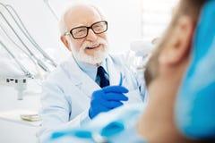 Feche acima de dentista experiente com dentes falsos à disposição imagens de stock
