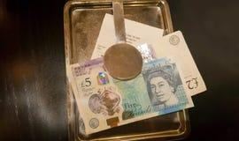 Feche acima de diversas contas das libras em um platte fotografia de stock royalty free