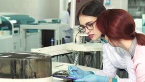 Feche acima de dois biólogos fêmeas que fazem anotações quando conduzir experimentar filme