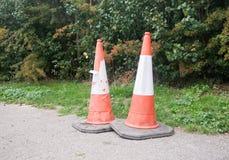 Feche acima de dois cones do tráfego no pavimento Imagens de Stock