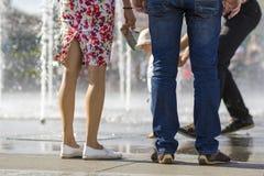 Feche acima de dois pares dos pés, menina no vestido curto com p floral Imagens de Stock Royalty Free
