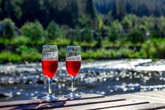 Feche acima de dois vidros do vinho tinto no fundo de um rio da montanha Sala de estar de madeira do chaise, montanhas, feriado l fotos de stock royalty free