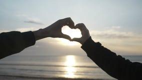 Feche acima de duas mãos do amante que fazem um coração para dar forma ao apreciar o por do sol e então ao guardar as mãos romant vídeos de arquivo