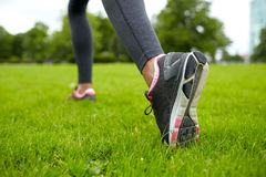 Feche acima de exercitar os pés da mulher na grama no parque imagens de stock