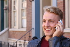 Feche acima de Guy Talking novo atrativo de sorriso a alguém que usa o telefone celular Imagens de Stock Royalty Free
