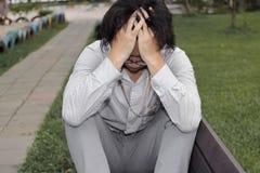 Feche acima de homem de negócio asiático novo forçado deprimido que sofre da depressão severa no parque fotos de stock