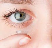 Feche acima de introduzir a lente de contato no olho fêmea fotografia de stock royalty free