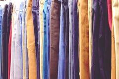 Feche acima de muitas calças de brim coloridas que penduram na cremalheira imagens de stock royalty free
