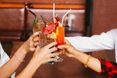 Feche acima de muitas mãos dos amigos que guardam um vidro do cocktail alcoólico para o recolhimento e a celebração do social na  imagens de stock