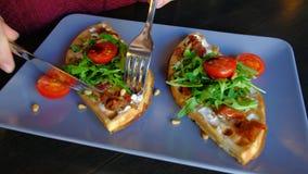Feche acima de - a mulher come os waffles do prato com espinafres, tomates de cereja no café filme