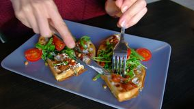 Feche acima de - a mulher come os waffles do prato com espinafres, tomates de cereja no café video estoque